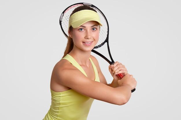 Ik ben klaar om te spelen! mooie gezonde actieve vrouw in de rechtbank cap, casual t-shirt, tennisracket houdt, kijkt positief direct naar camera, geïsoleerd over witte muur. mensen, hobby concept Premium Foto