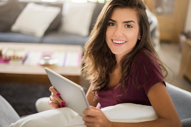 Ik breng graag tijd door in mijn woonkamer. vrouw met dgital tablet Gratis Foto
