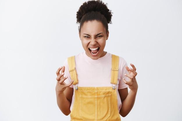 Ik ga je met blote handen wurgen. portret van boze en pissige emotionele afro-amerikaanse vrouw in trendy gele overall, gebaren met palmen van haat, schreeuwend van woede over grijze muur Gratis Foto