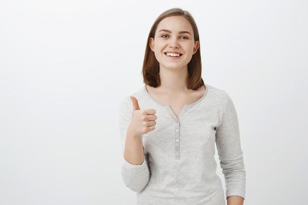 Ik geef een idee duimen omhoog. blij, vrolijke, charmante jonge europese vrouw met kort bruin haar glimlachend met een vrolijke uitdrukking die de goede uitstraling van een vriend leuk vindt terwijl ze een nieuwe outfit probeert goed te keuren over een grijze muur Gratis Foto