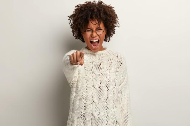 Ik geef jou de schuld! stressvolle afro-amerikaanse vrouw met knapperig, borstelig haar wijst direct wijsvinger, schreeuwt woedend, uit ergernis, staat over witte muur, zegt dat je schuldig bent Gratis Foto