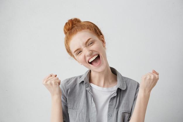 Ik heb het gehaald! gelukkig opgewonden positieve jonge vrouw balde vuisten en schreeuwen, verheugend op goed nieuws, haar succes of overwinning. mensen, levensstijl, levensdoelen, prestatie en geluksconcept Gratis Foto