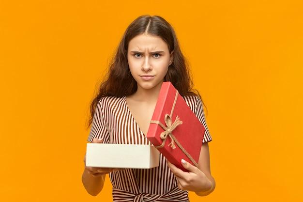 Ik hou er niet van. geïsoleerde shot van ontevreden stijlvolle jonge vrouw met golvend haar doos openen Gratis Foto