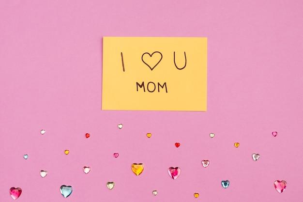 Ik hou van je mama titel op papier in de buurt van decoratieve harten Gratis Foto