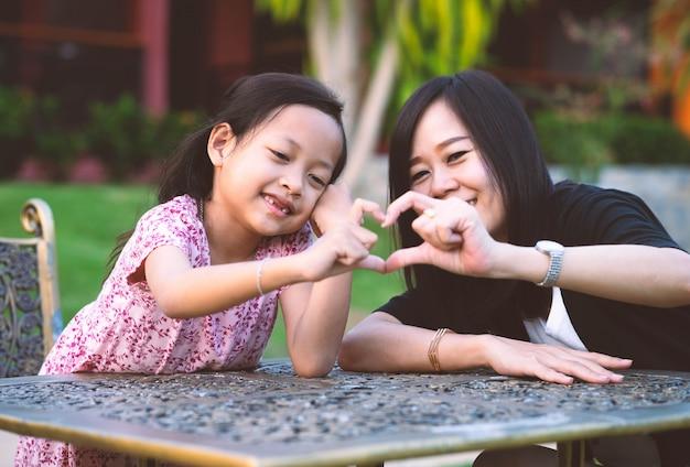 Ik hou van je moeder, dochter en moeder glimlach met hand maken hartsymbool. Premium Foto