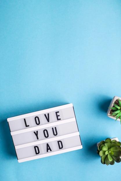 Ik hou van je vader is geschreven op een decoratieve lamp op een blauwe achtergrond Premium Foto