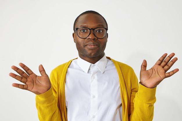 Ik weet het niet, who cares, niet mijn probleem. portret van clueless modieuze jonge afrikaanse man in bril en geel vest, onverschillig of onzeker gebaar makend. lichaamstaal Gratis Foto