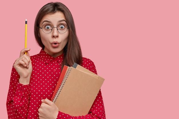 Ik weet wat ik moet schrijven! mooie verbaasde schrijver steekt hand op met potlood, draagt schoolboeken, spiraalvormig notitieblok, draagt een bril Gratis Foto