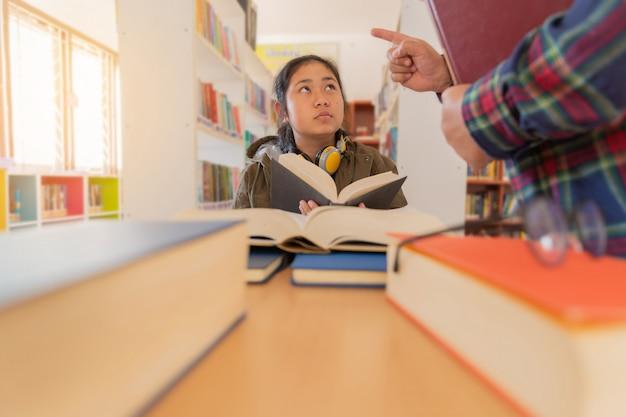 In de bibliotheek - man teacher leert de student in library Gratis Foto