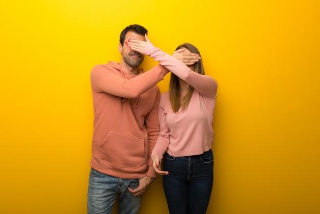 In de dag van de valentijnskaart groep van twee mensen op gele achtergrond die betrekking hebben op ogen door handen. verrast om te zien wat er gaat gebeuren Premium Foto