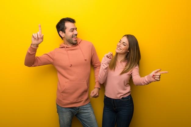 In de dag van de valentijnskaart groep van twee mensen op gele achtergrond genieten van dansen tijdens het luisteren naar muziek op een feestje Premium Foto