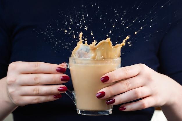 In de handen van het meisje een kopje koffie met melk. koffiespray. splash mooie vormen van koffiespatten. rode manicure. ontbijt tijd. Premium Foto
