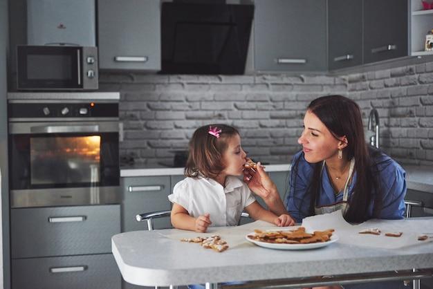 In de keuken en gelukkige familie. concept vakantie voedsel. moeder en dochter versieren koekjes. gelukkige familie bij het maken van zelfgemaakte gebak. zelfgemaakt eten en kleine helper Gratis Foto