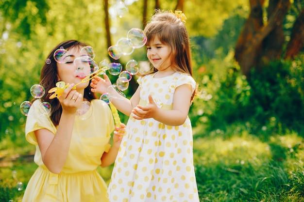 In een zomerpark bij groene bomen loopt mama in een gele jurk en haar kleine mooie meisje Gratis Foto