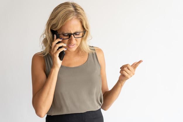 In verwarring gebrachte onderneemster die op telefoon en gesturing hand spreekt Gratis Foto