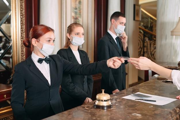 Inchecken hotel. receptioniste aan balie in hotel met medische maskers als voorzorgsmaatregel tegen coronavirus. jonge vrouw op zakenreis doet check-in in het hotel Premium Foto