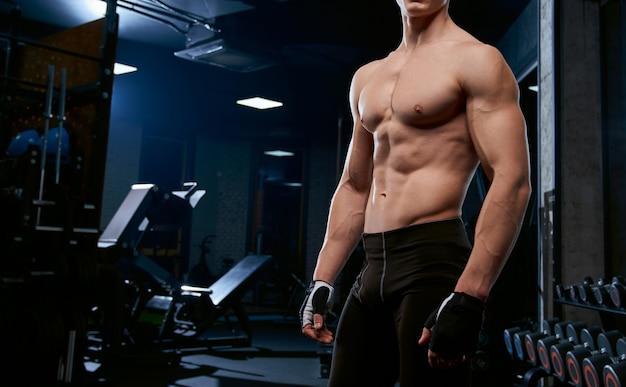 Incognito shirtless sportman poseren in de sportschool. Gratis Foto