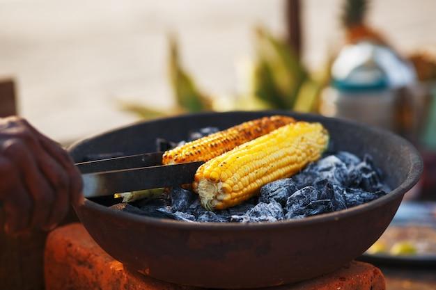 Indiaas eten op het strand - verse maïskolven worden geroosterd op de kolen. Premium Foto