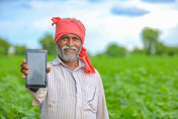 Indiase boer met een mobiel scherm op landbouwgebied Premium Foto