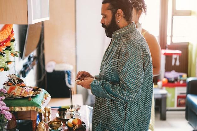 Indiase familie vieren religie hindoe-evenement thuis - zuid-aziatische culturen en levensstijl concept - focus op man gezicht Premium Foto
