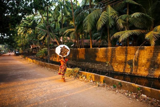 Indiase vrouw met een grote en zware zak kreupelhout op haar hoofd in een rode sari. het gaat langs het rivierkanaal met palmbomen. de ondergaande zon in gokarna Premium Foto