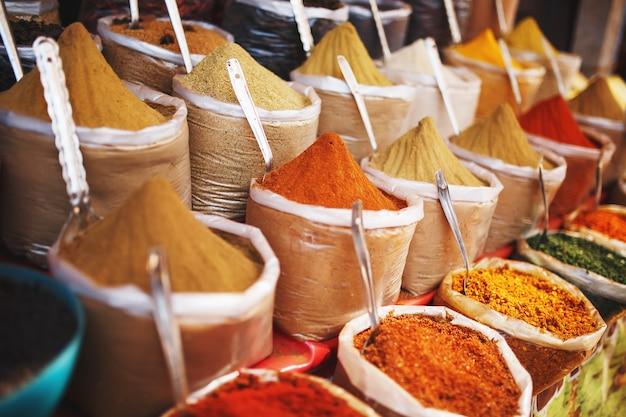 Indische gekleurde kruiden bij lokale markt. een verscheidenheid aan kruiden in verschillende kleuren en tinten, smaken en texturen op de kraampjes van de indiase markt Premium Foto