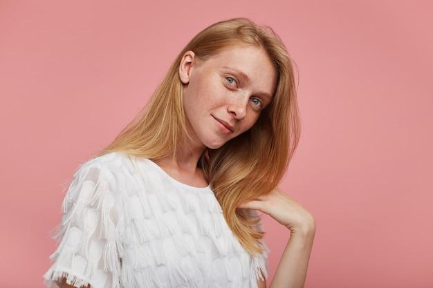 Indoor foto van charmante jonge roodharige vrouw met natuurlijke make-up gekleed in elegante slijtage positief naar de camera kijken en zacht glimlachend, geïsoleerd op roze achtergrond Gratis Foto