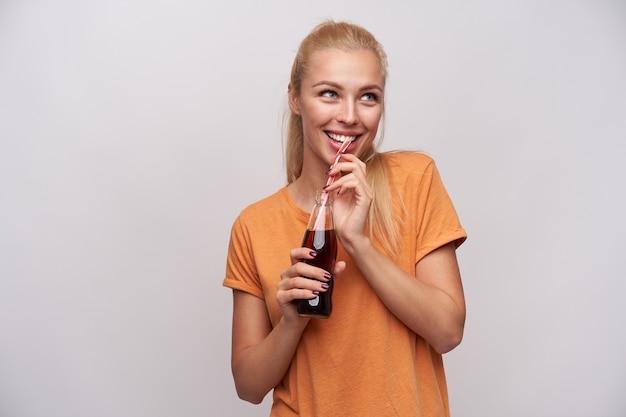 Indoor foto van jonge vrolijke blonde vrouw met paardenstaart kapsel glazen fles frisdrank in opgeheven handen houden en vrolijk opzij kijken, geïsoleerd op witte achtergrond Gratis Foto