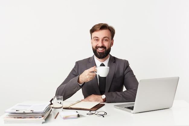 Indoor foto van positieve jonge bebaarde brunette man met een goede werkdag en gelukkig lachend naar voren zittend aan tafel over witte muur, kopje koffie houden tijdens de pauze Gratis Foto