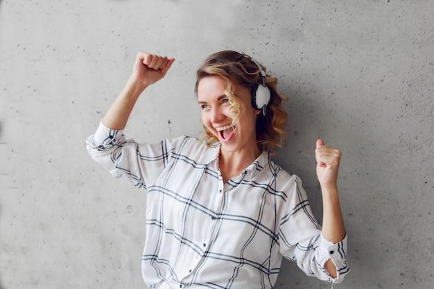 Indoor lifestyle portret van gelukkige enthousiaste vrouw luisteren naar muziek op stoel op grijze stedelijke muur achtergrond. Gratis Foto