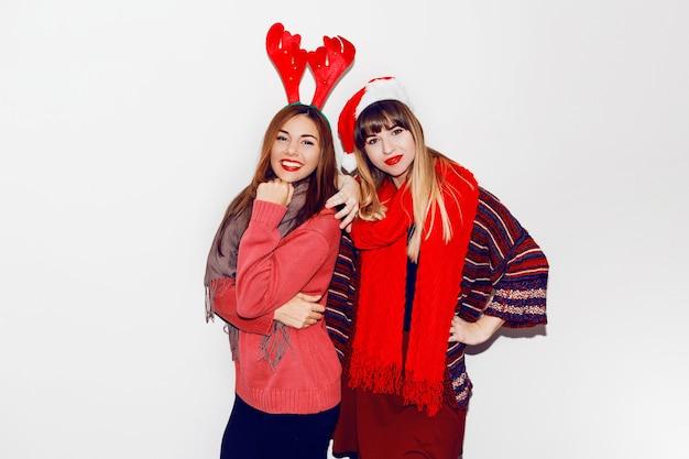 Indoor lifestyle portret van twee beste vrienden. vakantie make-up en leuke winter gezellige outfit, witte muur. maskeradehoeden dragen. Gratis Foto