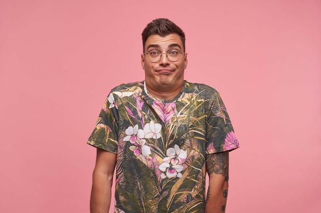 Indoor portret van aantrekkelijke man staande over de roze achtergrond met opgetrokken wenkbrauwen, schouderophalend en gezicht trekken, verveeld en onverschillig Gratis Foto