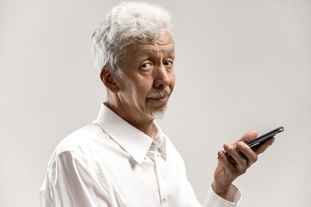 Indoor portret van aantrekkelijke senior man geïsoleerd op een grijze muur, met lege smartphone, met behulp van stembesturing, blij en verrast voelen. menselijke emoties, gezichtsuitdrukking concept. Gratis Foto
