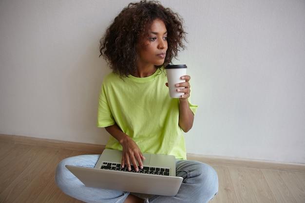 Indoor portret van donkere huid jonge mooie vrouw met papieren beker in de hand, hand op toetsenbord houden en bedachtzaam opzij kijken, spijkerbroek en geel t-shirt dragen Gratis Foto