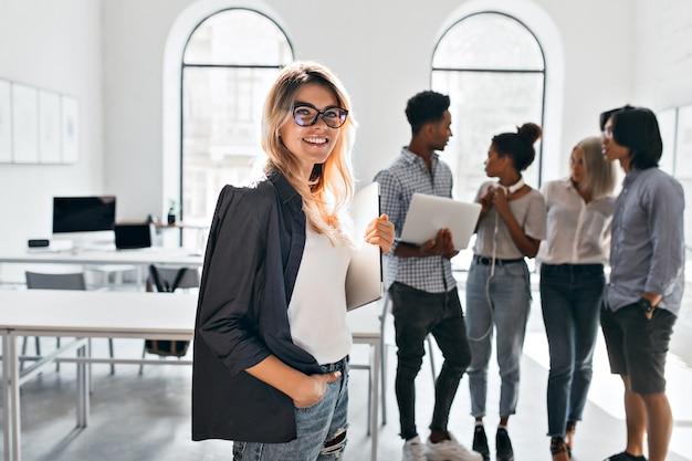 Indoor portret van elegante business-lady in zwarte jas en haar team. afrikaanse officemanager in witte sneakers met laptop en praten met mulat vrouw in spijkerbroek. Gratis Foto