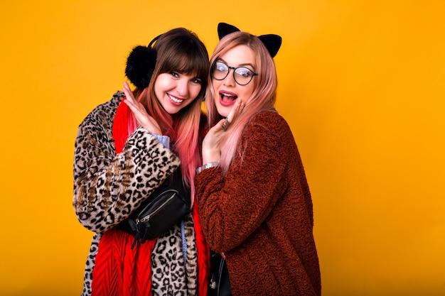 Indoor portret van gelukkige twee mooie vrouw die lacht en plezier heeft, super trendy bont teddyjassen en grappige warme oren draagt, winterstemming. Gratis Foto