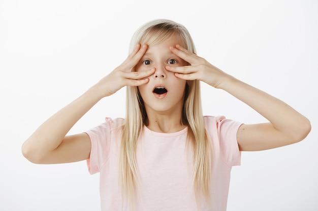 Indoor portret van geschokt verrast schattig blond meisje in roze t-shirt, kaak laten vallen, wauw zeggen terwijl ze vingers bij de ogen houdt Gratis Foto