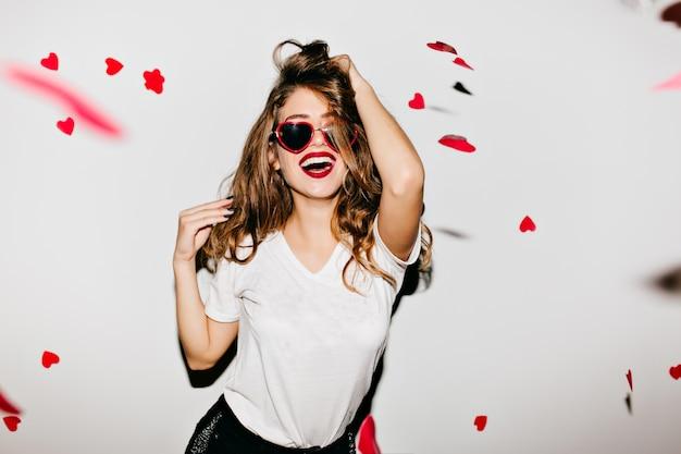 Indoor portret van geweldig vrouwelijk model in trendy t-shirt aan haar lange glanzende haren te raken Gratis Foto