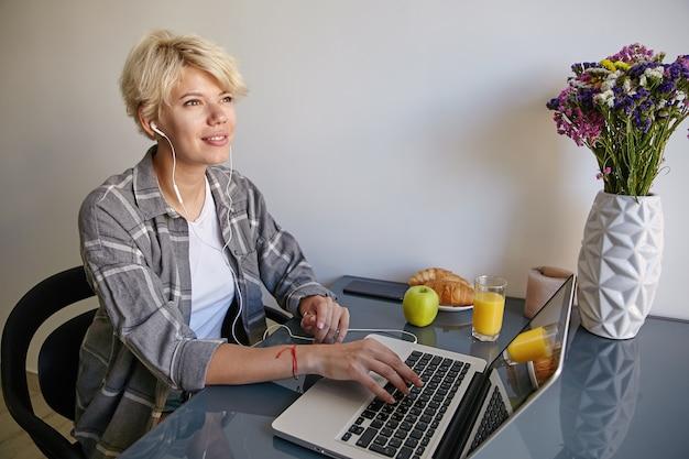 Indoor portret van mooie jonge vrouw in vrijetijdskleding zit naast laptop met koptelefoon, hand houden op toetsenbord en dromen over iets Gratis Foto
