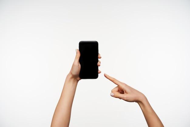 Indoor portret van mooie jonge vrouwelijke handen met mobiele telefoon en tonen op zwart scherm met wijsvinger, wordt geïsoleerd op wit Gratis Foto