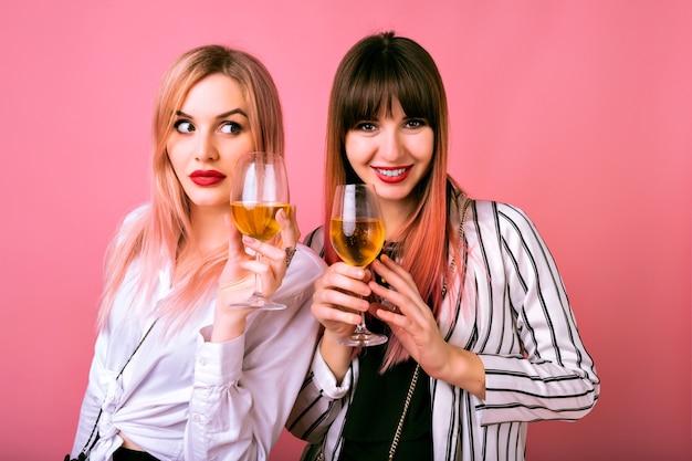 Indoor portret van twee gelukkige beste vrienden zusters vrouwen, trendy zwart-witte kleren dragen, gewaardeerd gezicht aanklagen Gratis Foto