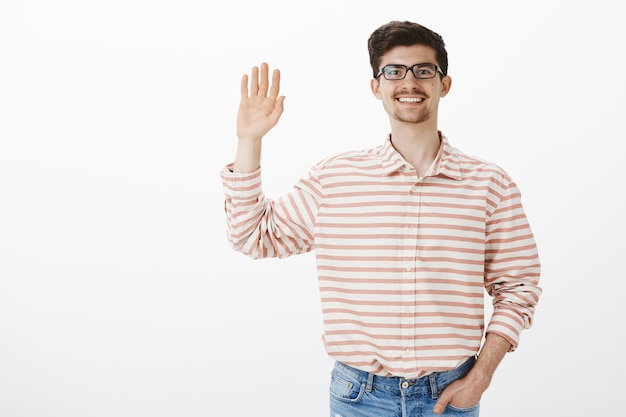 Indoor portret van vriendelijke gewone europese man met baard en snor in nerdy bril, palm omhoog en zwaaien, hallo zeggen tegen teamleden, begroetend personeel Gratis Foto