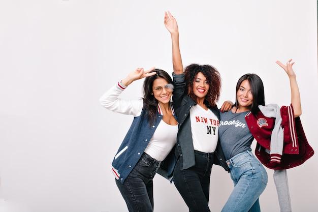 Indoor portret van vrij internationale vrienden grappige dansende en zwaaiende handen. aanbiddelijk aziatisch meisje in spijkerbroek weekend doorbrengen met universiteitsgenoten en poseren. Gratis Foto