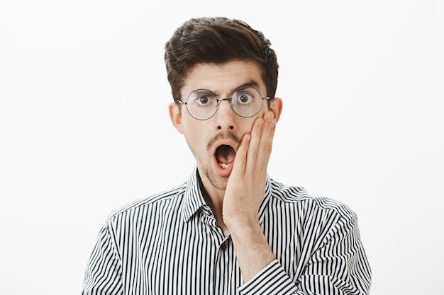 Indoor shot van geschokte emotionele volwassen mannelijke collega in bril, kaak laten vallen en palm op wang vasthouden, verrast en verbluft door waarheidsgetrouw verhaal van werknemer, staande verbaasd over grijze muur Gratis Foto