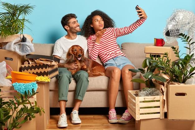 Indoor shot van liefdevolle familie paar maken selfie portret, afro vrouw blaast lucht kus in de camera van de smartphone, poseren op comfortabele bank met huisdier, verhuizen in nieuw modern appartement, dozen rond uitpakken Gratis Foto
