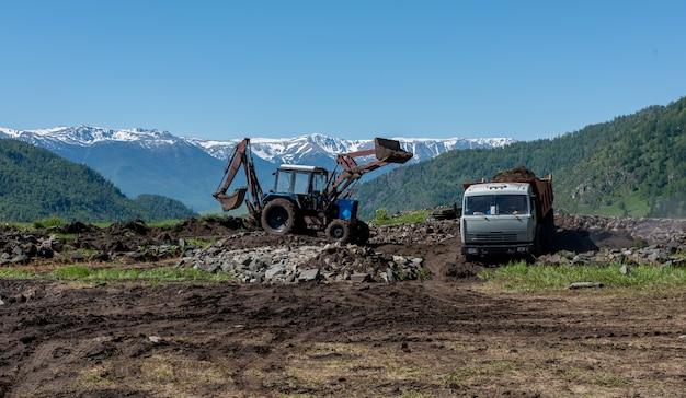 Industrieel graafwerktuig dat grond van zandbak in een vrachtwagen dumper laadt Premium Foto