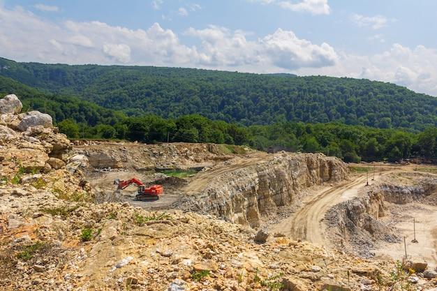 Industrieel landschap met een graafmachine in een steengroeve voor de winning van kalksteen, gips en marmer op een zomerse dag Premium Foto