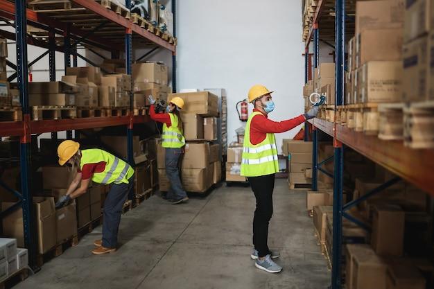 Industriële arbeiders in het magazijn die veiligheidsmaskers dragen voor coronaviruspreventie - focus op de mens Premium Foto