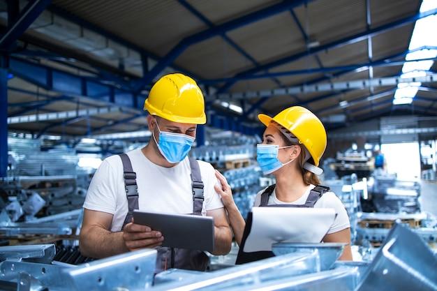 Industriële arbeiders met gezichtsmaskers beschermd tegen coronavirus analyseren resultaten van productie in fabriek Gratis Foto