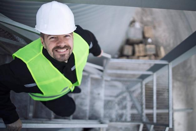 Industriële fabrieksarbeider in beschermende uitrusting staande op metalen trap van productie-installatie Gratis Foto